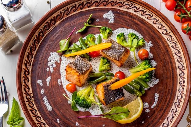 Gebakken zalm op chia-saus met broccoli, wortelen, kersentomaten en slabonen, horizontale foto, hoogste mening