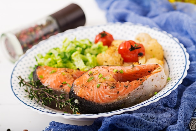 Gebakken zalmsteak met bloemkool, tomaten en kruiden. goede voeding.