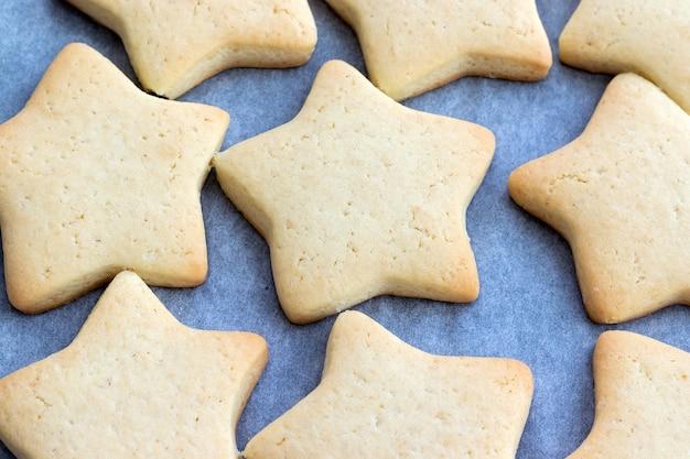 Gebakken zandkoekjes in de vorm van sterren op een bakplaat