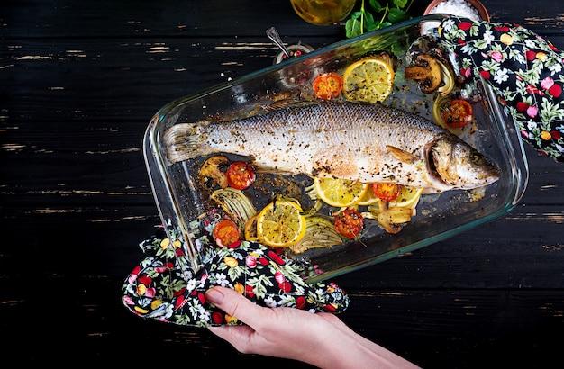 Gebakken zeebaars in een ovenschaal met kruiden en groenten om in handen te houden.
