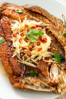 Gebakken zeebaars vis met vissaus en pittige salade op bord