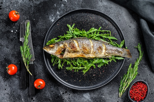 Gebakken zeebaars vissen met rucola op zwarte tafel.