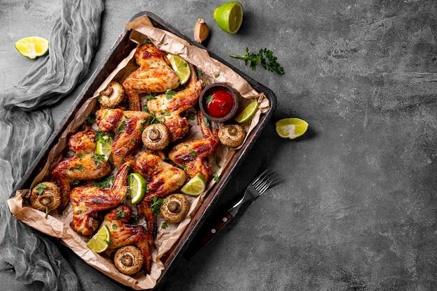 Gebakken zelfgemaakte kippenvleugels met champignons en limoen, bovenaanzicht, kopieer ruimte voor tekst. hoge kwaliteit foto