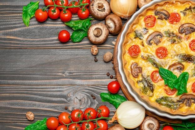Gebakken zelfgemaakte quiche taart in keramische bakken vorm op concrete achtergrond