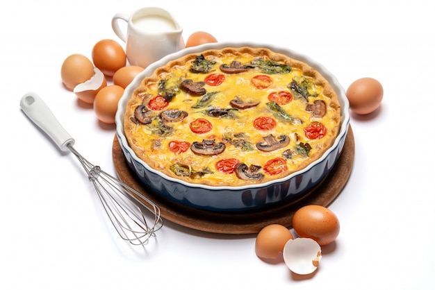 Gebakken zelfgemaakte quichetaart in keramische bakvorm, eieren en room