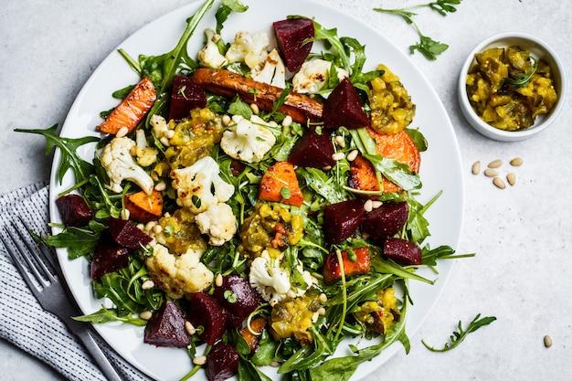 Gebakken zoete aardappel, bloemkool en rode bietensalade met mosterddressing in een witte plaat, exemplaarruimte. gezond veganistisch voedselconcept.