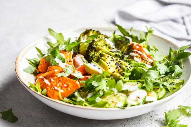 Gebakken zoete aardappel, broccoli en avocado slakom met tahin dressing.