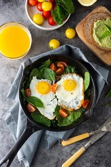 Gebakken zonnige eieren met spinazie, avocadotoost en verse tomaten, gezond ontbijtvoedsel,