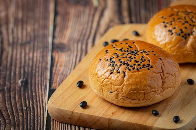 Gebakken zwarte bonenpasta broodjes op houten snijplank