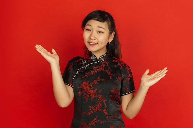 Gebaren, gasten uitnodigen. gelukkig chinees nieuwjaar. aziatisch jong meisje portret op rode achtergrond. vrouwelijk model in traditionele kleding ziet er gelukkig uit. viering, menselijke emoties. copyspace.