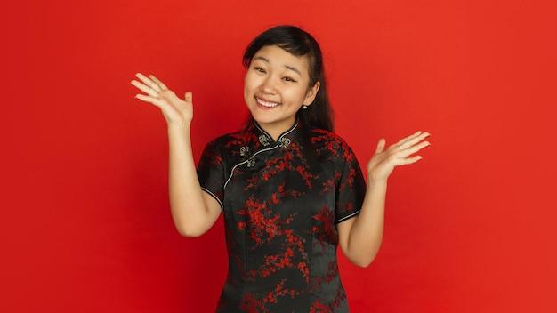 Gebaren, glimlachen, uitnodigend. gelukkig chinees nieuwjaar. aziatisch jong meisje portret op rode achtergrond. vrouwelijk model in traditionele kleding ziet er gelukkig uit. viering, menselijke emoties. copyspace.