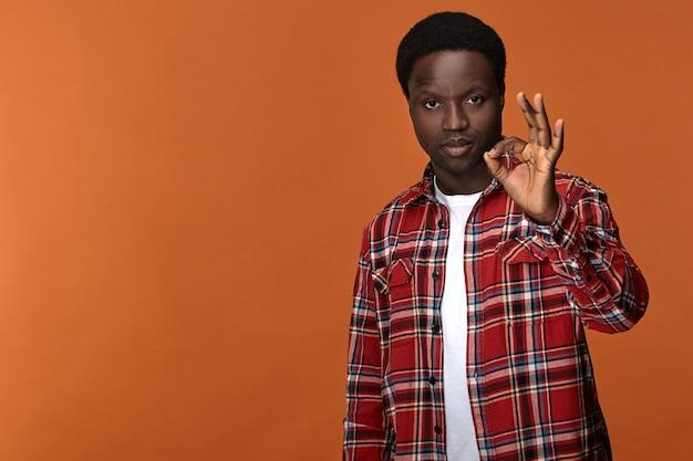 Gebaren, tekens, symbolen en lichaamstaal. zelfverzekerd ernstig aantrekkelijk afrikaans amerikaans mannetje dat duim en wijsvinger verbindt in cirkel, zeggend dat alles in orde is.