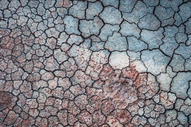 Gebarsten blauwe muur met rood zand erop