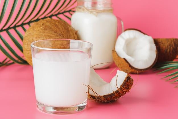 Gebarsten coco en kokosmelk in glas op heldere roze achtergrond