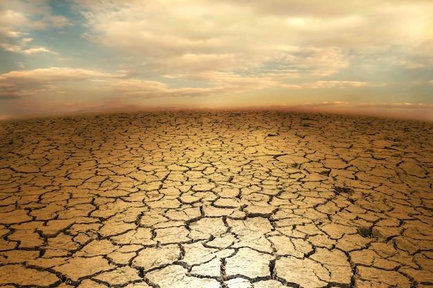 Gebarsten de woestijnterrein van de grondaarde met hemel
