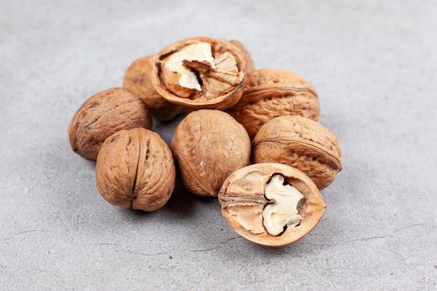 Gebarsten en hele walnoten opgestapeld op marmeren oppervlak