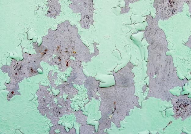 Gebarsten en schil van groene kleurenverf op staal met geroeste textuur en achtergrond
