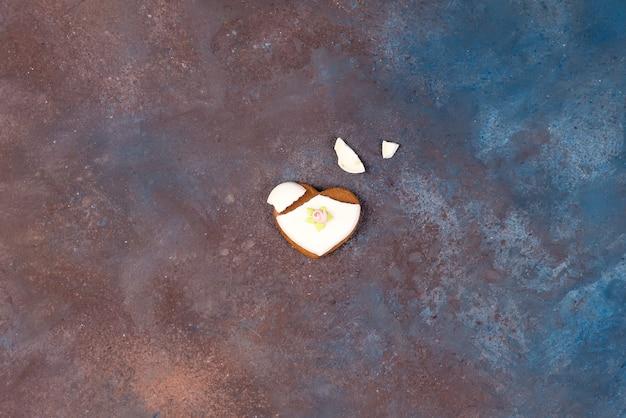 Gebarsten hartvormig koekje dat met suikerglazuur als concept van gebroken hart wordt verfraaid
