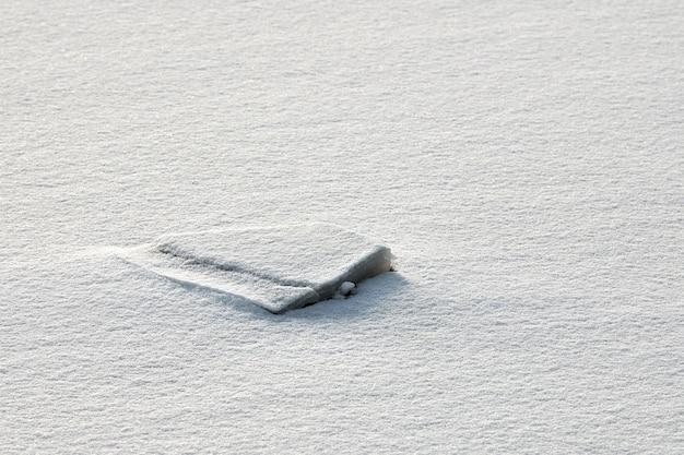 Gebarsten ijs van bevroren meer met witte sneeuw bovenop
