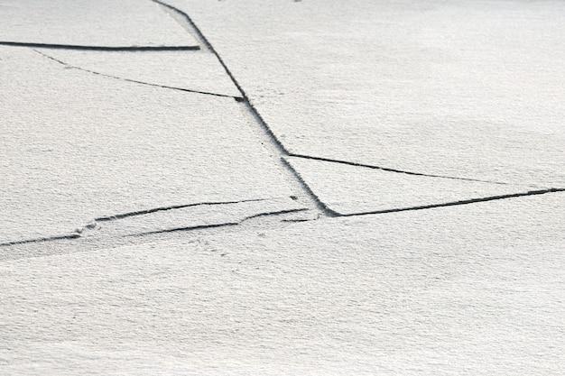 Gebarsten ijs van bevroren meer met witte sneeuw erop
