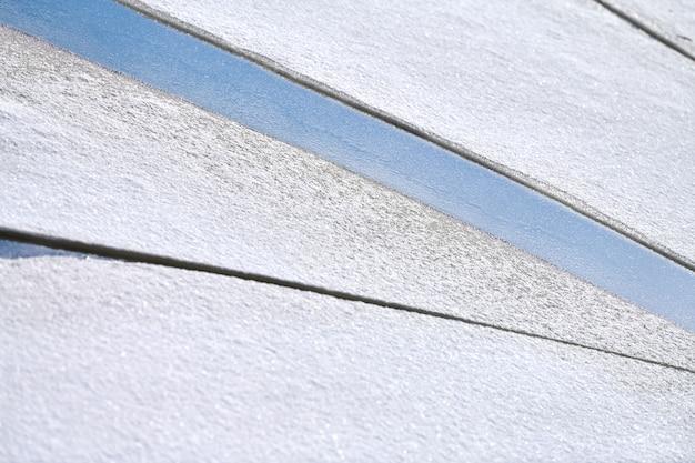 Gebarsten ijs van bevroren rivier met witte sneeuw bovenop en blauw water eronder. de achtergrond van de ijstextuur, sluit omhoog.