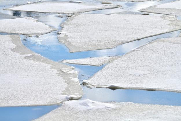 Gebarsten ijs van bevroren rivier met witte sneeuw bovenop en blauw water eronder