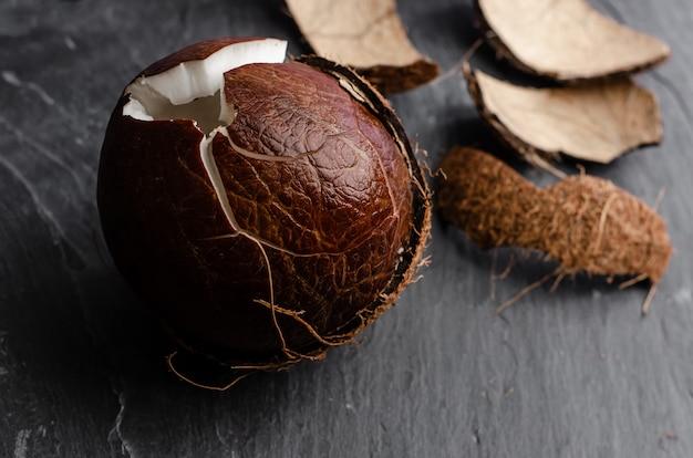 Gebarsten kokosnoot op donkere steenachtergrond.