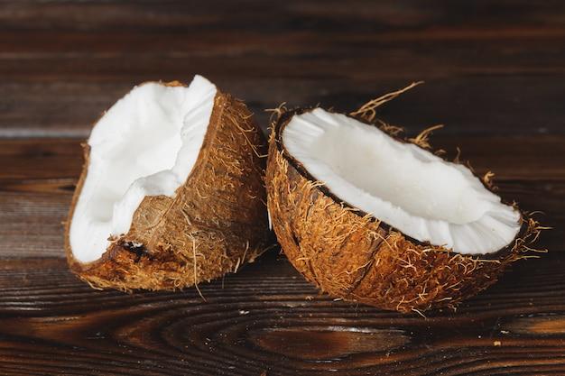 Gebarsten kokosnootstukken op donkere houten achtergrond