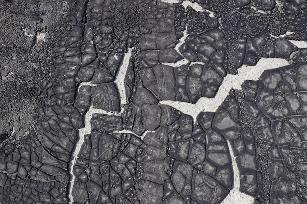 Gebarsten oud asfaltmateriaal. toegepast op een betonnen ondergrond. scheuren in de hars zijn het bewijs van de tijd.
