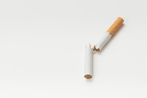 Gebarsten sigaret boven witte achtergrond