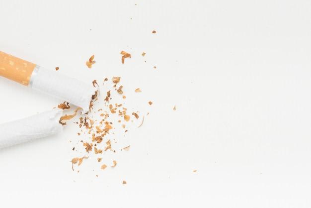 Gebarsten sigaret en tabak boven witte achtergrond