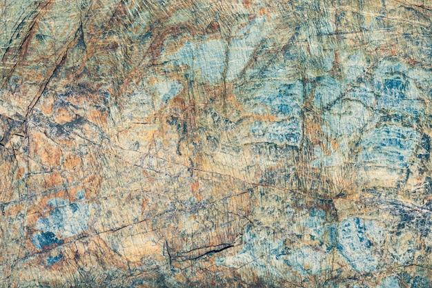 Gebarsten stenen oppervlak bruine, grijze en blauwe kleur. close-up macro weergave van natuur patroon textuur of achtergrond genomen in natuurlijke omgeving. door de jaren heen verweerd, uniek effect getextureerd ontwerp
