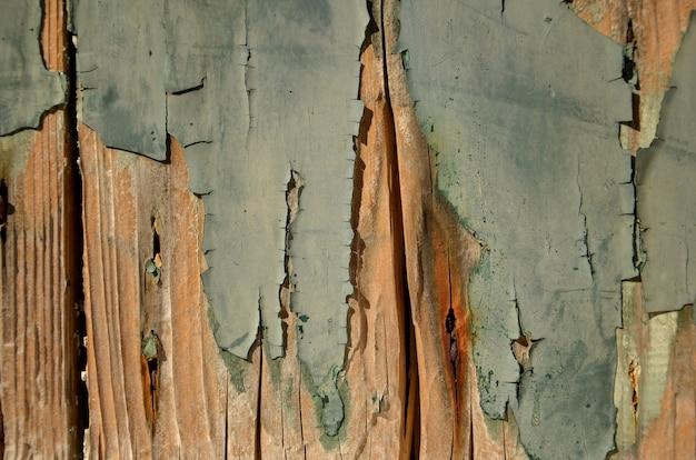 Gebarsten verf op een houten muur. grunge achtergrond. verweerd hout lichtgroen en oranje