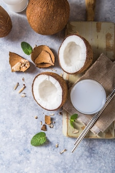Gebarsten verse kokosnoot, melk en plaknoot op concrete achtergrond, ruimte voor tekst voedselingrediënten, gezonde levensstijl, paradijs