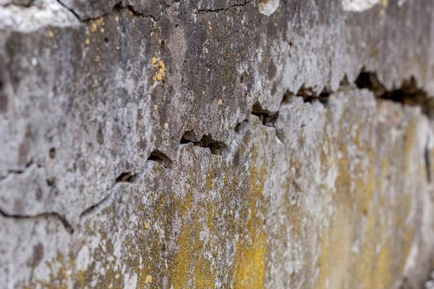 Gebarsten witte muur textuur achtergrond, zeer oude muur met een barst erop.