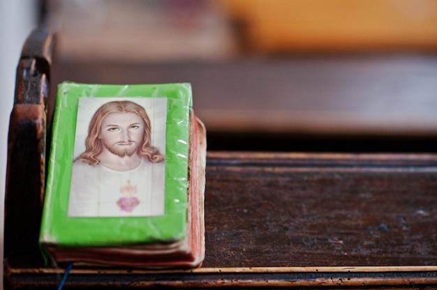 Gebedboek met jezus christus op omslag bij bank in de kerk