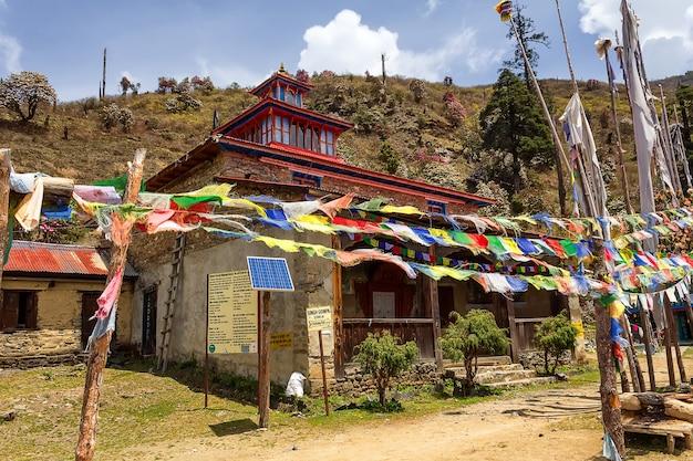 Gebedsvlaggen, zonnepanelen en huis langs een bergpad in langtang, nepal. himalaya