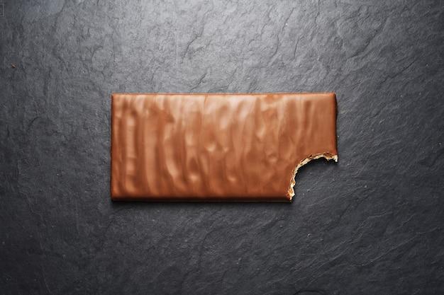 Gebeten bruine melkchocoladereep op zwarte leiachtergrond. bovenaanzicht
