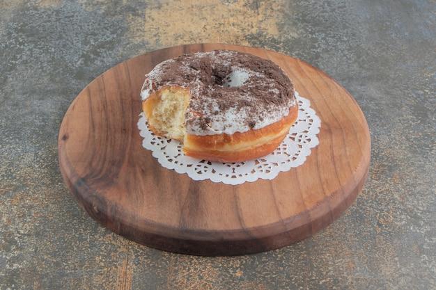 Gebeten donut op een houten bord