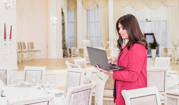 Gebeurtenismanager die laptop in banketzaal met behulp van