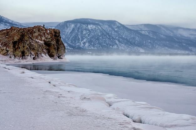 Gebied van ijsheuveltjes en rots op het bevroren meer baikal. zonsondergang