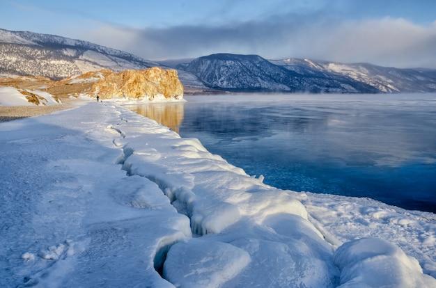 Gebied van ijsheuveltjes en rots op het bevroren meer baikal. zonsopkomst