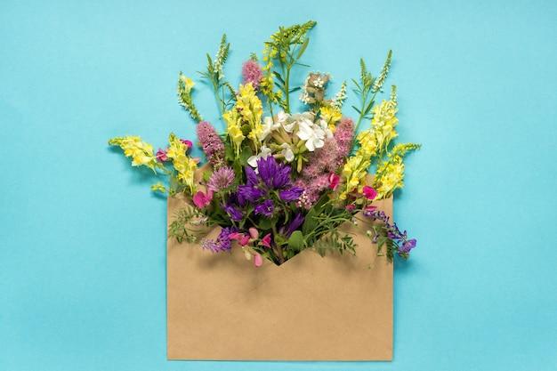 Gebieds kleurrijke rustieke uitstekende bloemen in ambachtenvelop op blauw