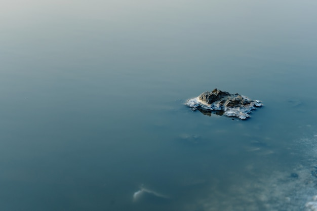 Gebieds mening van eiland in zout meer. mooie kleuren van de natuur. fototafel voor op reis. gedroogd zeezout in het water.