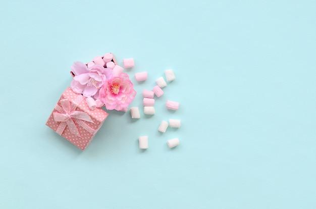 Gebloeide roze giftdoos bestrooid met heemst op blauwe achtergrond