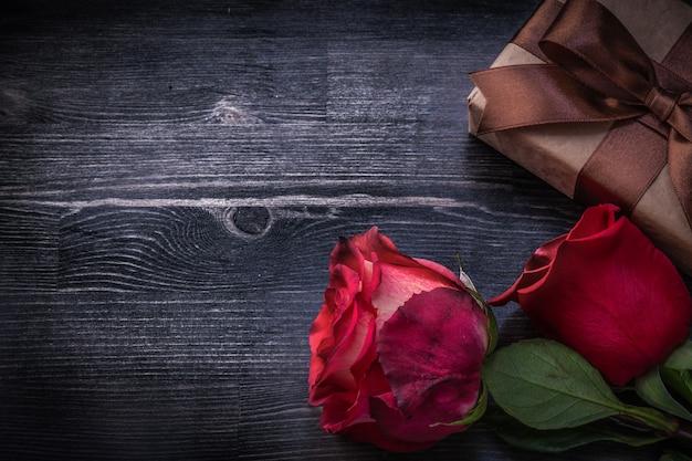 Gebloeide rozen verpakte giftdoos op houten achtergrondvakantieconcept