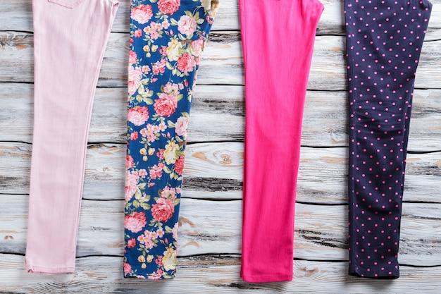 Gebloemde en lichtroze broek. stijlvolle damesbroek met print. zomerkleding op witte vloer. geïmporteerde goederen van hoge kwaliteit.