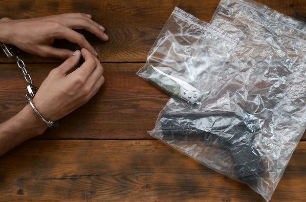 Geboeid handen van criminele verdachte op houten tafel en pistool met mes in transparante plastic verpakkingen als bewijsmateriaal van een plaats delict voor onderzoek