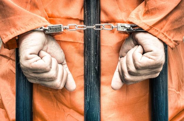 Geboeid handen van een gevangene achter de tralies van een gevangenis met oranje kleren