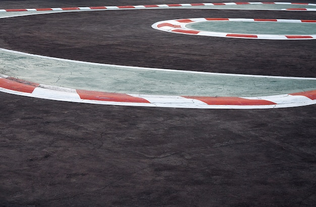 Gebogen asfalt rode en witte stoeprand van een racecircuit detail, motorsports racecircuit race track curve weg voor autoracen
